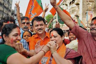 BJP workers celebrate their party's victory in North-East Assembly elections, outside state party headquarters in Kolkata on Sunday. Photo: PTI
