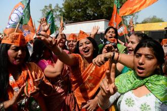 BJP supporters celebrate following northeast results outside the party headquarters in Delhi on Saturday. Photo: AFP
