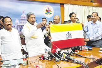 Karnataka chief minister Siddaramaiah with the Karnataka flag. Once approved, Karnataka will become only the second state to have a separate flag, after Jammu and Kashmir. Photo: PTI
