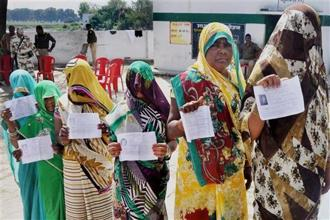 Voters display their voter's ID card at a polling booth for Phulpur bypoll elections in Allahabad on Sunday. Photo: PTI