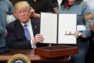 US President Donald Trump showing his signature on Section 232 proclamations on steel and aluminium imports on 8 March. Photo: AFP
