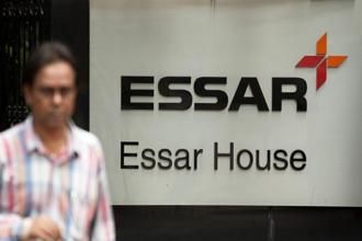 A pedestrian passes in front of the Essar Group corporate offices in Mumbai. Russian oil major Rosneft, fund UCP and Swiss commodities trader Trafigura bought Essar Oil's large refinery, 3,500 fuel stations and infrastructure for $12.9 billion last year. Photo: Bloomberg