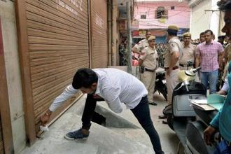 Municipal Corporation of Delhi official seals a shop at Gandhi Nagar during a sealing drive in East Delhi on Thursday. Photo: PTI