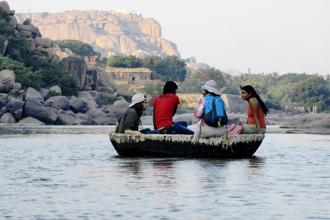 Travellers take a coracle ride on the Tungabhadra river, overlooking the ruins of Hampi. Photo: iStockphoto
