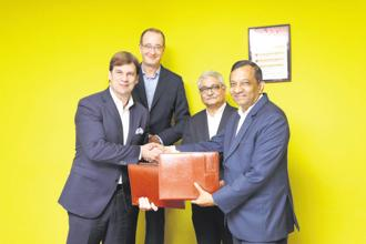 Mahindra's Pawan Goenka (right) and Ford Motor executive vice-president Jim Farley (left) after signing their deal on Thursday. The two automobile firms will co-develop a small electric car for India.