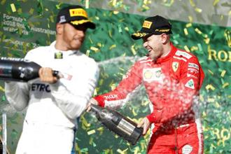 Ferrari driver Sebastian Vettel (right) of Germany and Mercedes driver Lewis Hamilton of Britain spray champagne at the Australian Formula One Grand Prix in Melbourne on Sunday, 25 March, 2018. Vettel won ahead of Hamilton. Photo: AP