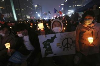 A girl holds a banner during a rally demanding peace on the Korean Peninsula near US embassy in Seoul, South Korea on Saturday. Photo: AP