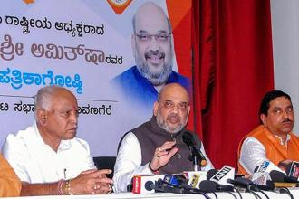 BJP president Amit Shah, flanked by B.S. Yeduyurappa (left) and BJP MP Prahlad Joshi in Davanagere, Karnataka, on Tuesday. Photo: PTI