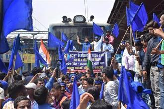 The members of the Bhim Army Sena stop a train during 'Bharat Bandh' call given by the Dalit organisations against the alleged 'dilution' of the SC/STs (Prevention of Atrocities) Act 1989, in Patna on Monday. Photo: PTI
