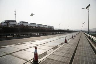 A car carrier trailer drives past as solar panels sit beneath transparent material in photovoltaic lanes developed by Qilu Transportation Development Group Co. on a highway in Jinan, China, 9 March, 2018. Photo: Bloomberg