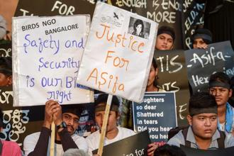 People hold placard and wear black ribbons during a protest against the rape and murder of a 8-year-old girl in Kathua, in Bengaluru on Monday. Photo: PTI