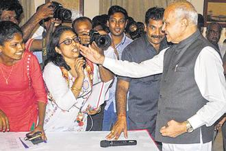 Tamil Nadu governor Banwarilal Purohit pats journalist Lakshmi Subramanian on her cheek in Chennai on Tuesday. Photo: PTI
