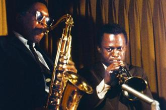 Miles Davis plays his trumpet beside tenor saxophonist John Coltrane. Photo: Getty Images