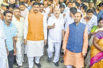 Union minister Prakash Javadekar (right) and Karnataka BJP chief B.S. Yeddyurappa try to pacify the supporters of the latter's son B.Y. Vijayendra, who failed to get a ticket for the assembly polls, in Mysuru on Tuesday. Photo: PTI