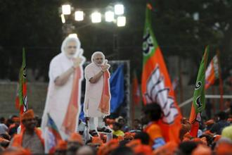 BJP supporters hold cut-out photographs of Prime Minister Narendra Modi during an election campaign rally in Bangalore on Tuesday. Photo: AP