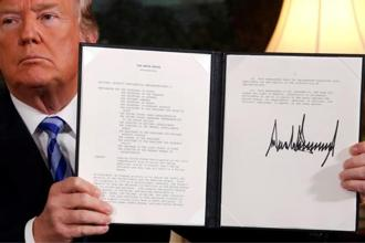 US President Donald Trump holds up a proclamation declaring his intention to withdraw from the JCPOA Iran nuclear agreement after signing it in the Diplomatic Room at the White House in Washington. Photo: Reuters