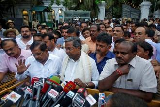 Outgoing chief minister of Karnataka Siddaramaiah (C) and Janata Dal (Secular) leader H.D. Kumaraswamy (R) speak with the media outside the governor's house in Bengaluru. Photo: Reuters