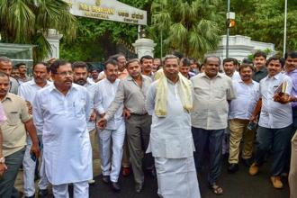 Outgoing Karnataka CM Siddaramaiah, JD(S) President H.D. Kumaraswamy with other leaders after meeting with governor Vajubhai Vala after the Karnataka election results, in Bengaluru on Tuesday. Photo: PTI