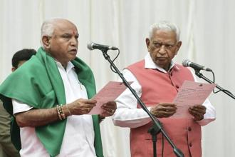 Karnataka  governor Vajubhai Vala administers oath to BJP leader B. S. Yeddyurappa as chief minister of the state at a ceremony in Bengaluru on Thursday. Photo: PTI