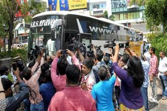 Media surrounds the bus as Karnataka Congress and JD(S) MLAs arrive at Taj Krishna Hotel, in Hyderabad on Friday. Photo: PTI