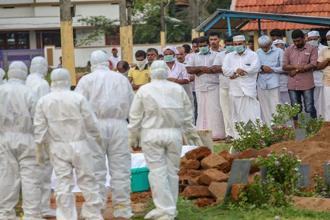 Relatives and hospital officals wear safety masks as they perform the last rites of V Moosa (61), a 'Nipah' virus victim, at Kannam Parambu graveyard, in Kozhikode, on Thursday. Photo: PTI