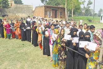 Voters line up at a polling booth in Bijnor, Uttar Pradesh, for the Noorpur assembly bypoll on Monday. Photo: PTI