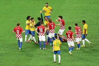 Brazil's Neymar is shown a yellow card after elbowing Croatia's Luka Modric during the opening match of the 2014 World Cup. Photo: Action Images