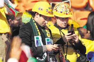 Football fans check their mobile phones during a match at the 2010 Fifa World Cup. Photo: Alamy