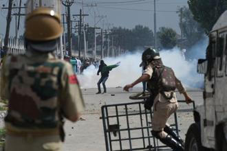 Police paramilitary troopers stand guard as Kashmiri youths protest during clashes in Srinagar on Saturday. Photo: AFP