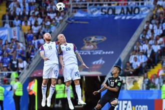 Iceland's Aron Gunnarsson and Emil Hallfredsson head the ball next to Argentina midfielder Maximiliano Meza during their match against Argentina in Moscow. Photo: AFP