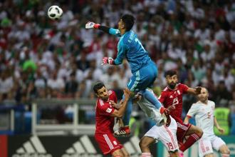 Iran's goalkeeper Alireza Beiranvand punches the ball away during their match against Spain. Photo: AFP
