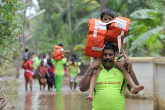 Kerala and Tamil Nadu Fire Force personnel carry children on their shoulders through flood waters during a rescue operation in Annamanada village in Thrissur, Kerala, on Sunday. Photo: AFP