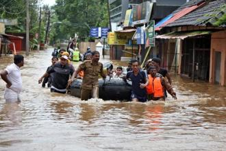 Rescuers evacuate people from a flooded area to a safer place in Aluva in Kerala, 18 August. Photo: Reuters
