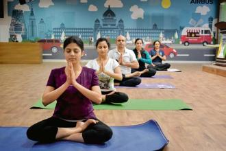 Employees at the Airbus Bengaluru office practising yoga in the multi-purpose room. Photo: Jithendra M/Mint