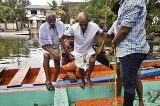 Fisherman and rescue personnel evacuate people in Alappuzha district on Monday. Raj K. Raj/HT