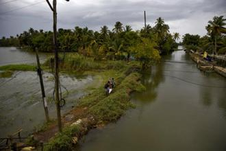 Two Indian youth walk to clean their flood affected homes as water levels recede in Kuttanad, Alappuzha in Kerala. Photo: AP