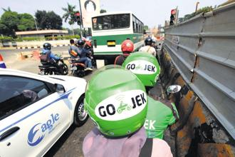Go-Jek got its start with ride-hailing and has since added a range of on-demand services that lets users pay bills, order food and buy movie tickets. Photo: Bloomberg
