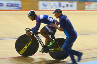 Track cyclists usually lean on their trainers for balance at the race starting point. Here, national coach R.K. Sharma helps Esow with his start at the Track Asia Cup. Photo: Ramesh Pathania/Mint