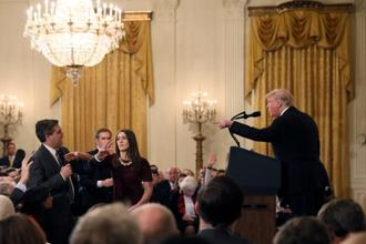 A White House staff member reaches for the microphone held by CNN's Jim Acosta as he questions US President Donald Trump on November 7. Photo: Reuters