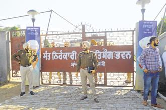 Punjab police personnel outside the Nirankari Bhawan in Rajasansi village following a grenade attack on Sunday.  Photo: AFP
