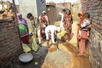 Resident Ali Mohammad, center, mixes cement during the construction of a toilet block, one of the first in the village and built with assistance from Sulabh International Social Service Organisation, in Chapra village, Haryana. Photo: Bloomberg