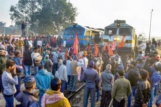 Activists block a train during the strike in Guwahati on Tuesday. PTI
