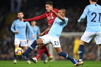 Liverpool's Roberto Firmino (in red) vies with Manchester City's Fernandinho during the Premier League match at the Etihad Stadium on 3 January. Photo: AFP