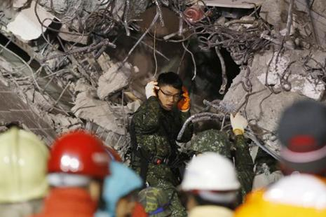 An army soldier tries to listen to signs of life in a collapsed building from an earthquake in Tainan, Taiwan, Sunday. Photo: AP