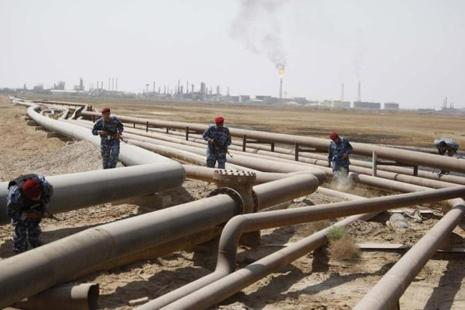 Policemen check oil pipelines during a patrol in Shueiba refinery in Iraq's Basra. Future prices of oil is often at the heart of geopolitical tussles and can contribute to inflation or trigger deflation. Photo: Reuters