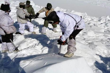 In this handout photograph released by the defence ministry on 8 February an Indian Army soldier cuts through ice and snow in the search for survivors after a deadly avalanche on the Siachen glacier. Photo: AFP