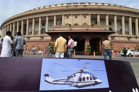 A placard bearing a picture of AgustaWestland chopper lying at a lawn after a protest by NDA members over AgustaWestland scam during the Parliament session in New Delhi. Photo: PTI
