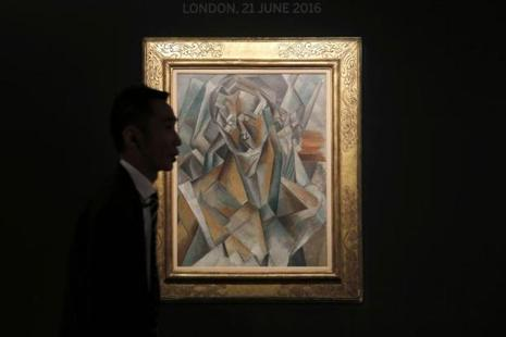 A security guard walks past the painting Femme Assise by painter Pablo Picasso during a media preview for the Sotheby's London Evening Auction Sale, in Hong Kong. Photo: AP