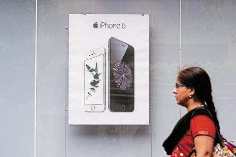 A pedestrian walks past an Apple iPhone 6 advertisement at an electronics store in Mumbai. Photo: Shailesh Andrade/Reuters