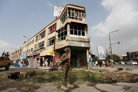 An Afghan security force personnel stands guard in front of a damaged building a day after a suicide attack in Kabul, Afghanistan, on Sunday. Photo: Reuters